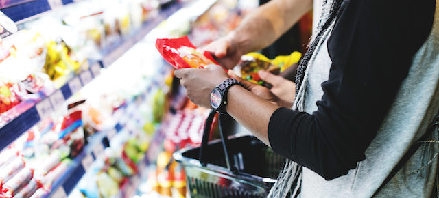 couple purchasing processed foods at a grocery store.