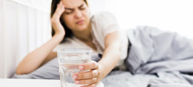 woman grabbing for a glass with a hangover